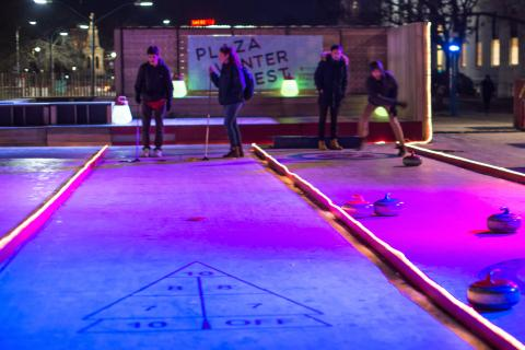 Photograph of people playing shuffleboard and curling on synthetic ice lanes on the Science Center Plaza at night with glowing lights