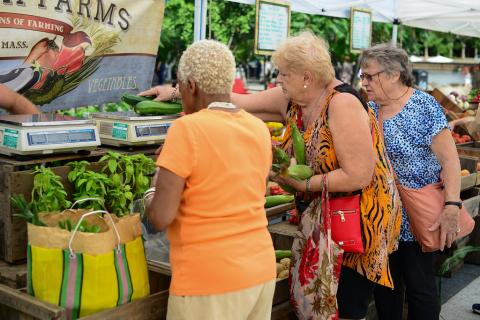 Women shopping at a vegetable stand at the Farmers' Market at Harvard